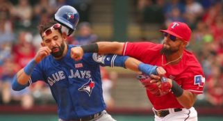 Jose Bautista dazed by a surprise revenge punch by Texas Rangers