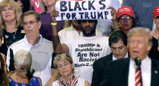 Who really is that man waving 'Blacks for Trump' sign at rallies?
